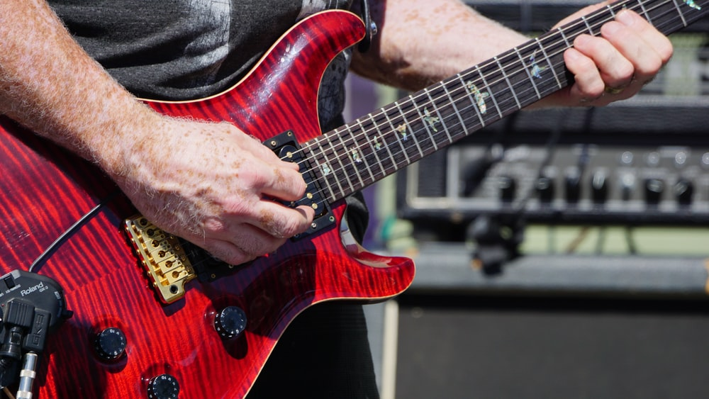 person playing a red stratocaster guitar during daytime