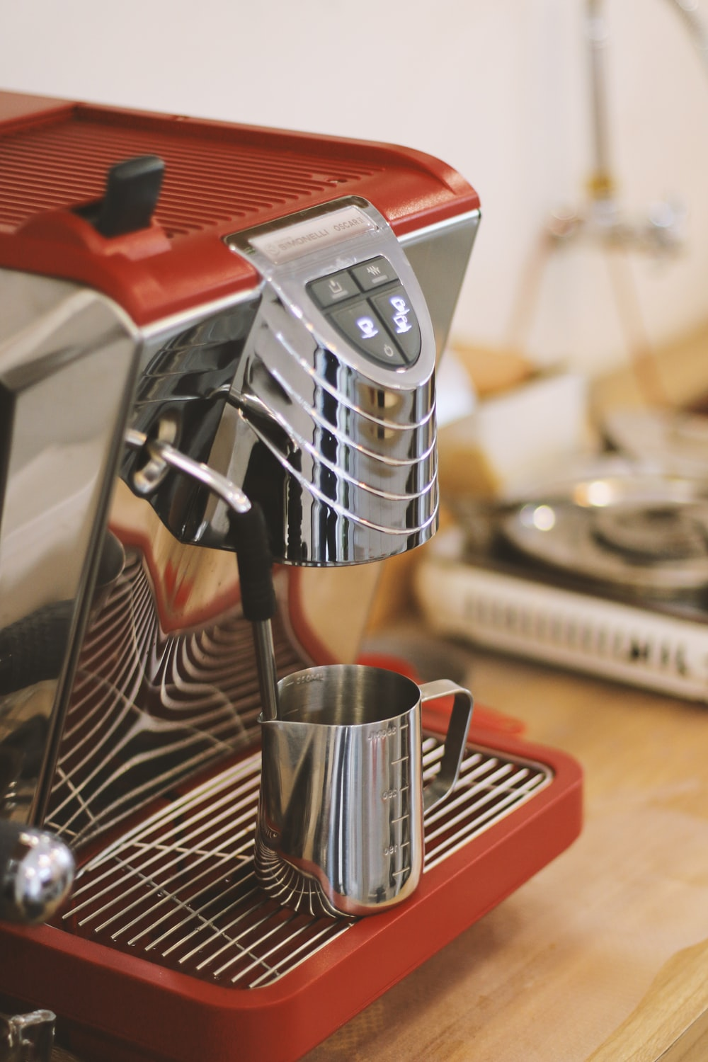 cup near red and gray stainless steel coffee maker