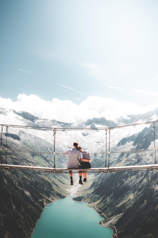 man and woman sitting on hanging bridge at daytime