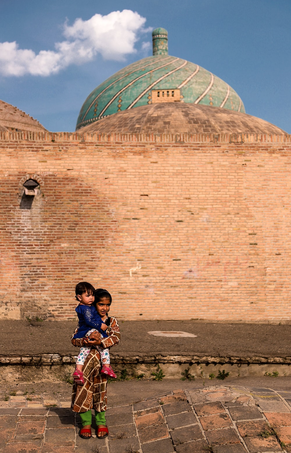 girl carrying toddler standing beside brown and green dome building