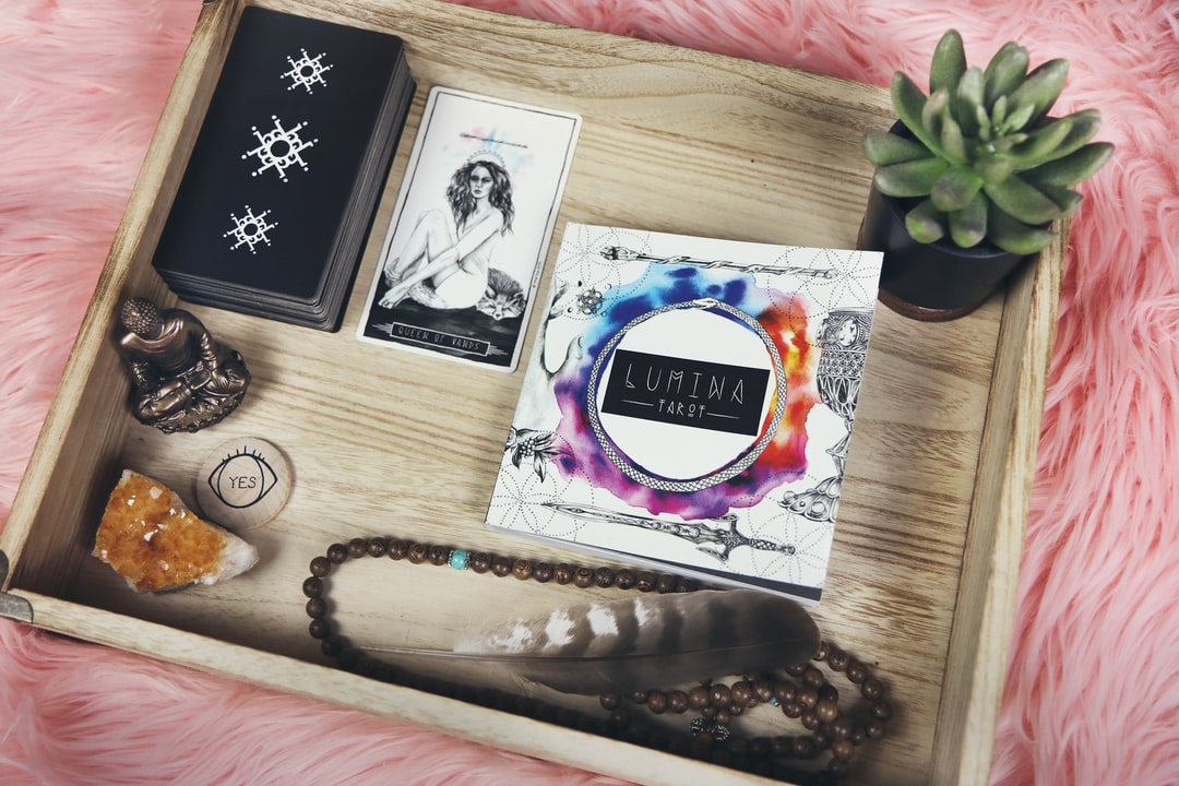 Wooden tray on pink fur, filled with gemstones, tarot cards, beads, feather, buddha statue and succulent - an alter of alternative worship of sorts.