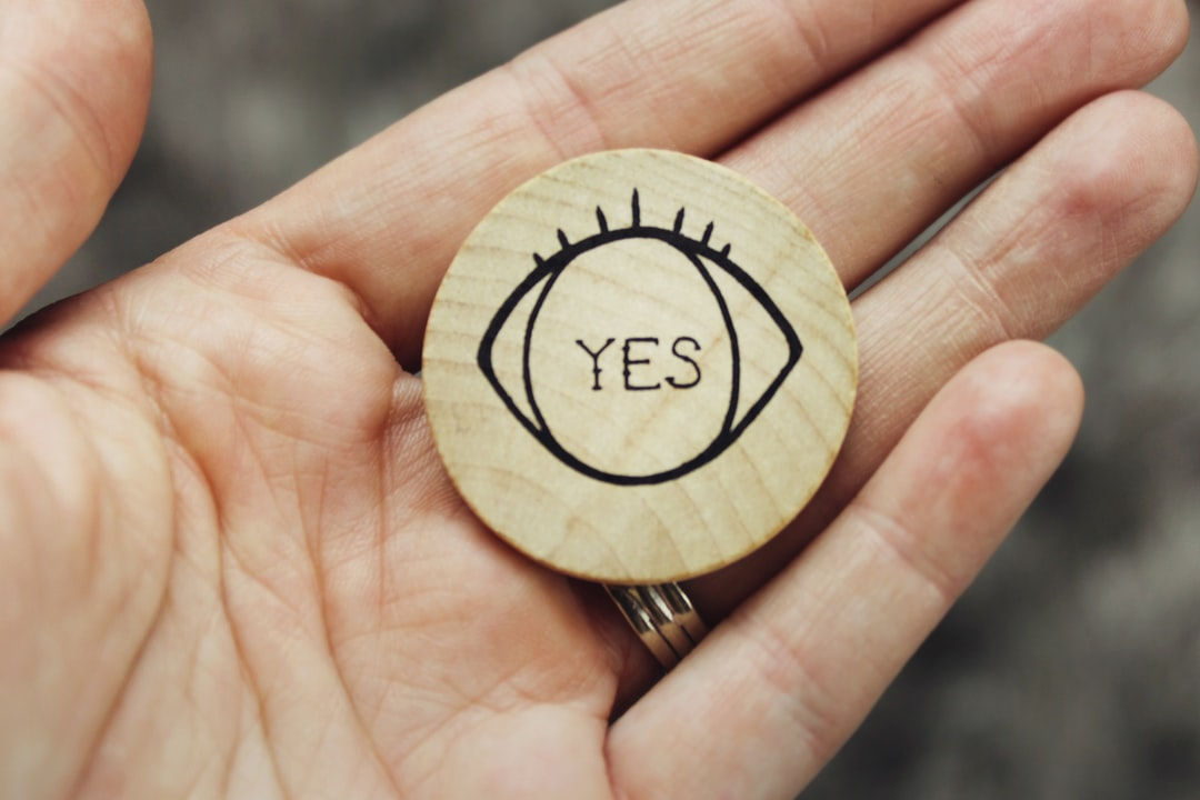 "Round wooden coin with eye detail and word, text ""yes"" printed on it, held in the palm of a woman's hand."