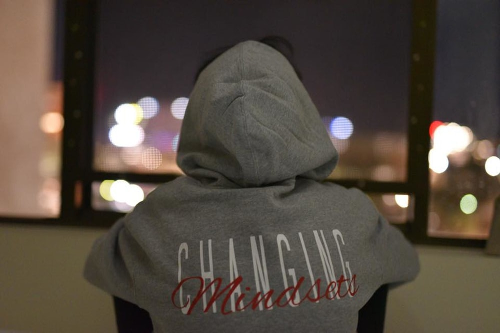 person wearing gray and red hooded jacket facing back