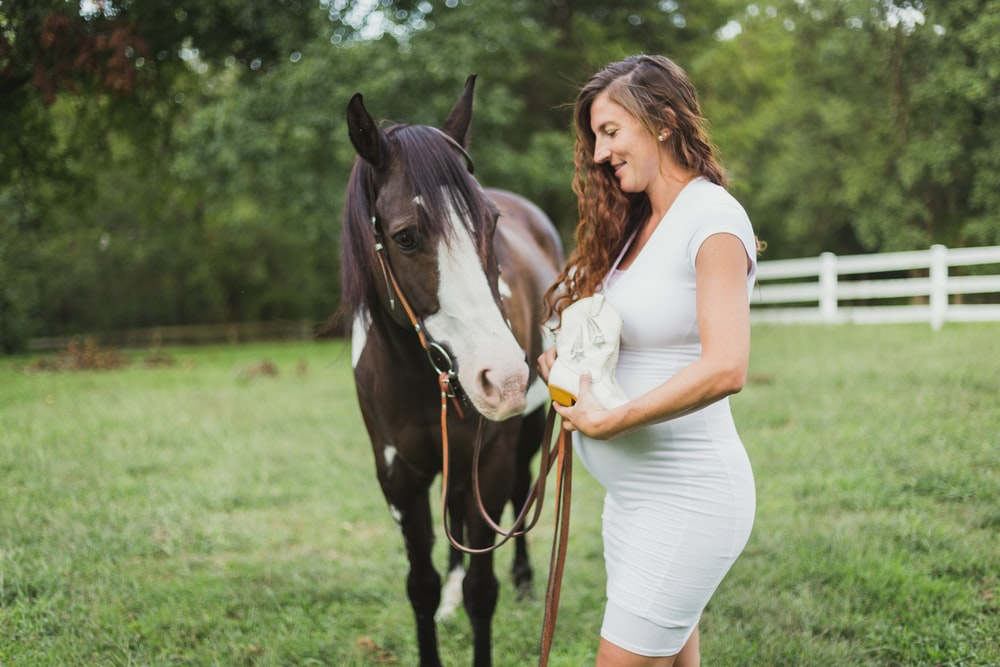 pregnant woman standing beside horse