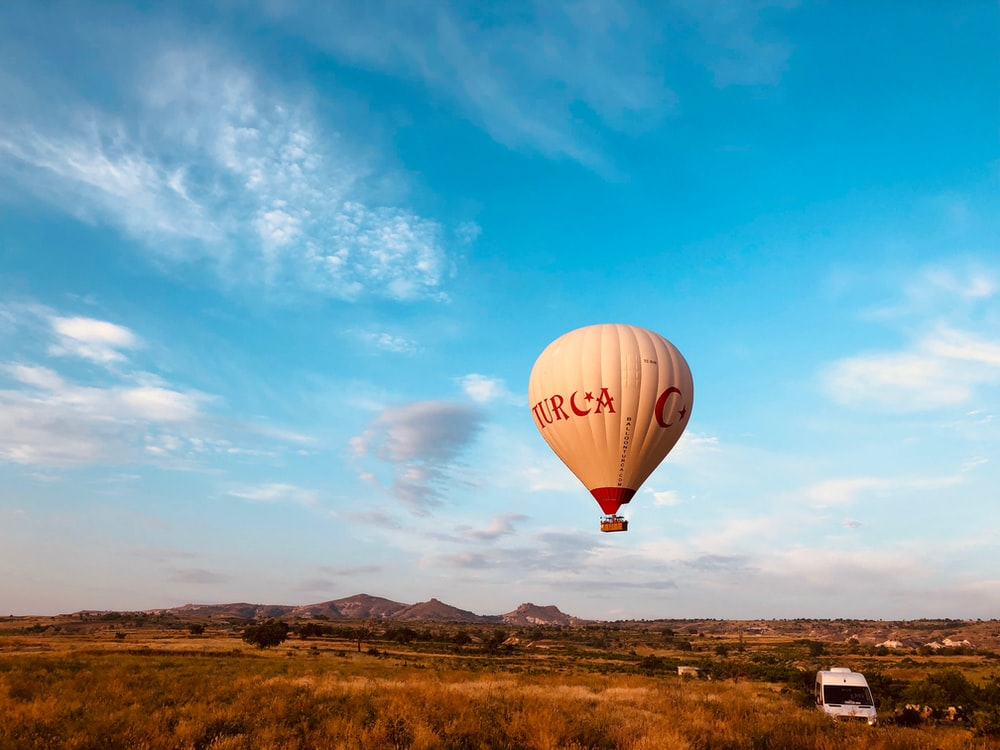 hot air balloon in mid air above vehicle during day