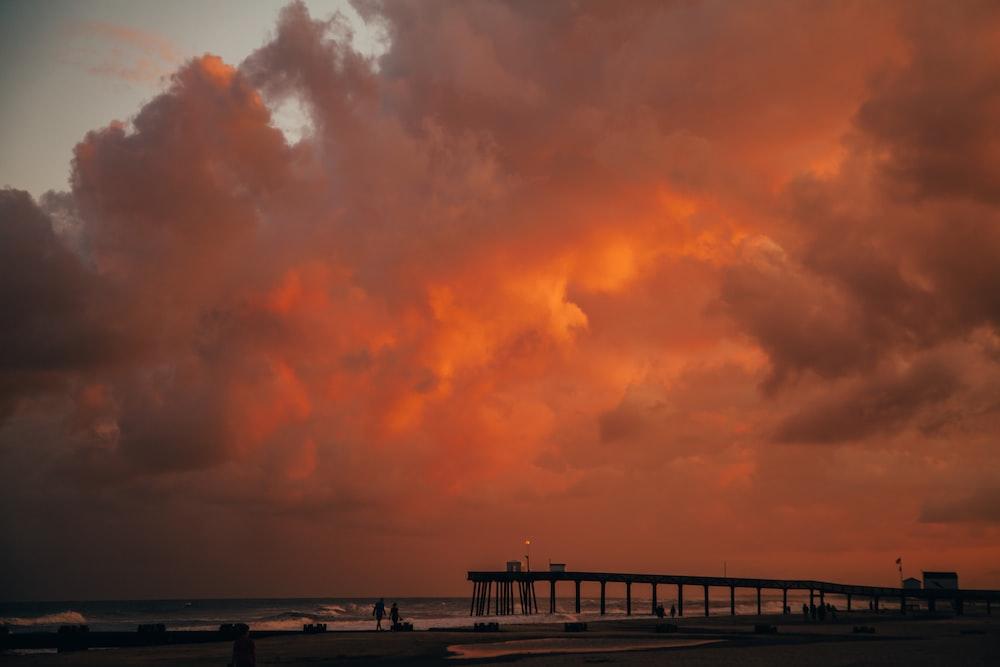 beach dock viewing sea under orange skies