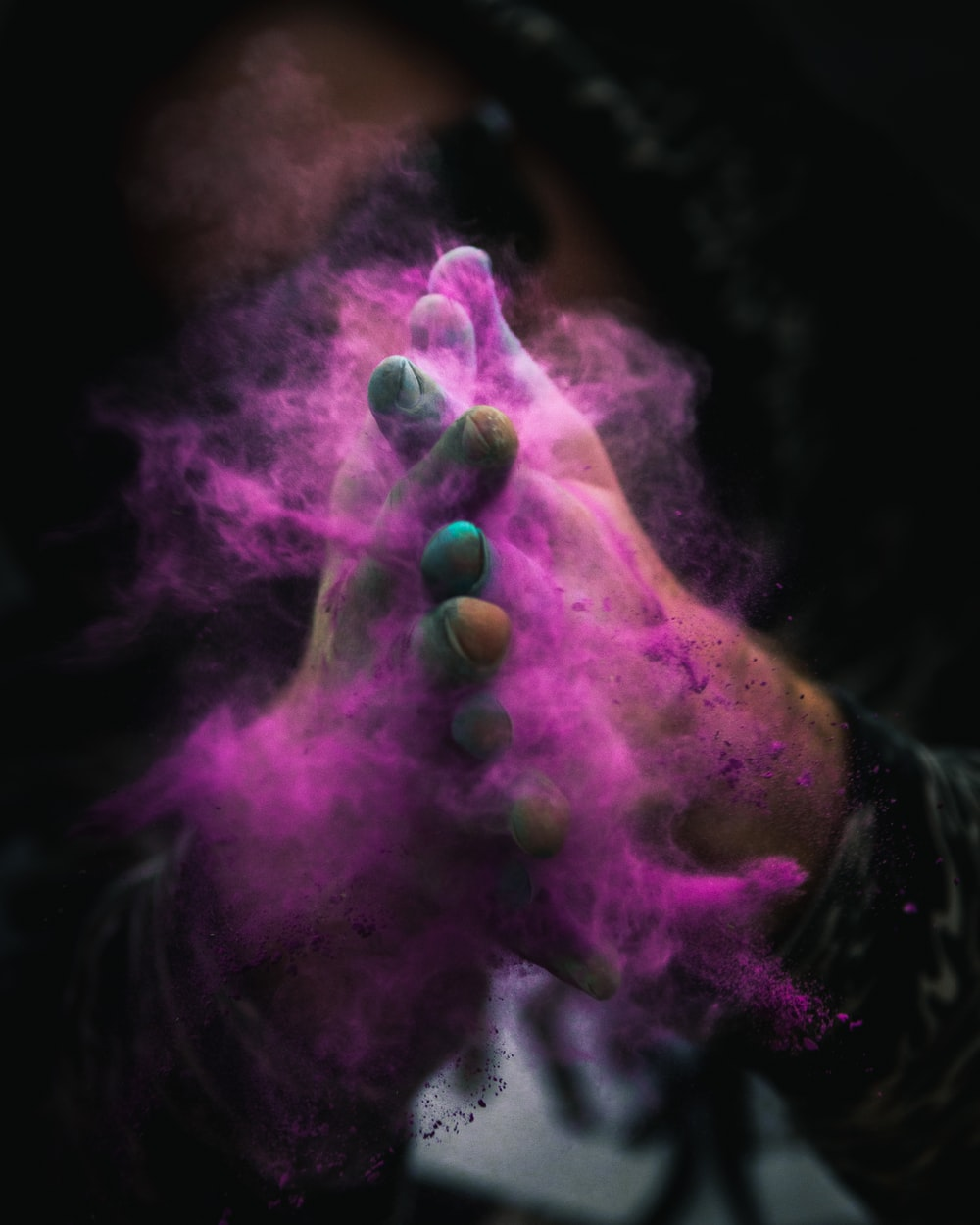 person with colored powders on hands