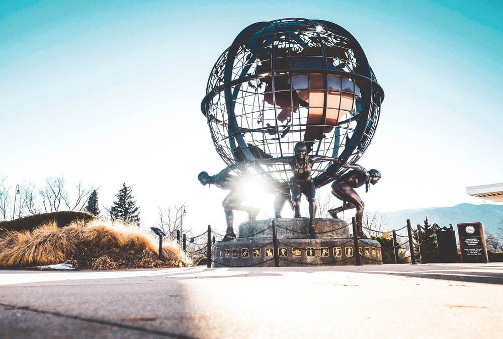 men carrying globe statue during daytime