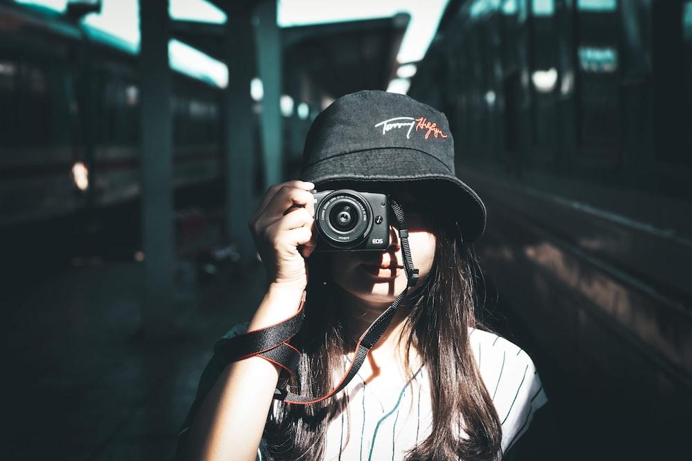 woman wearing black bucket hat holding camera