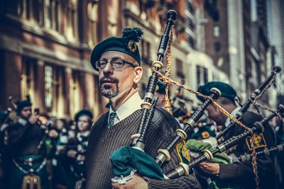 close-up photography of man carrying instrument bagpipe teams background