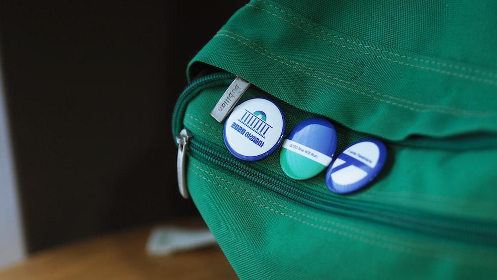 green badges on bag