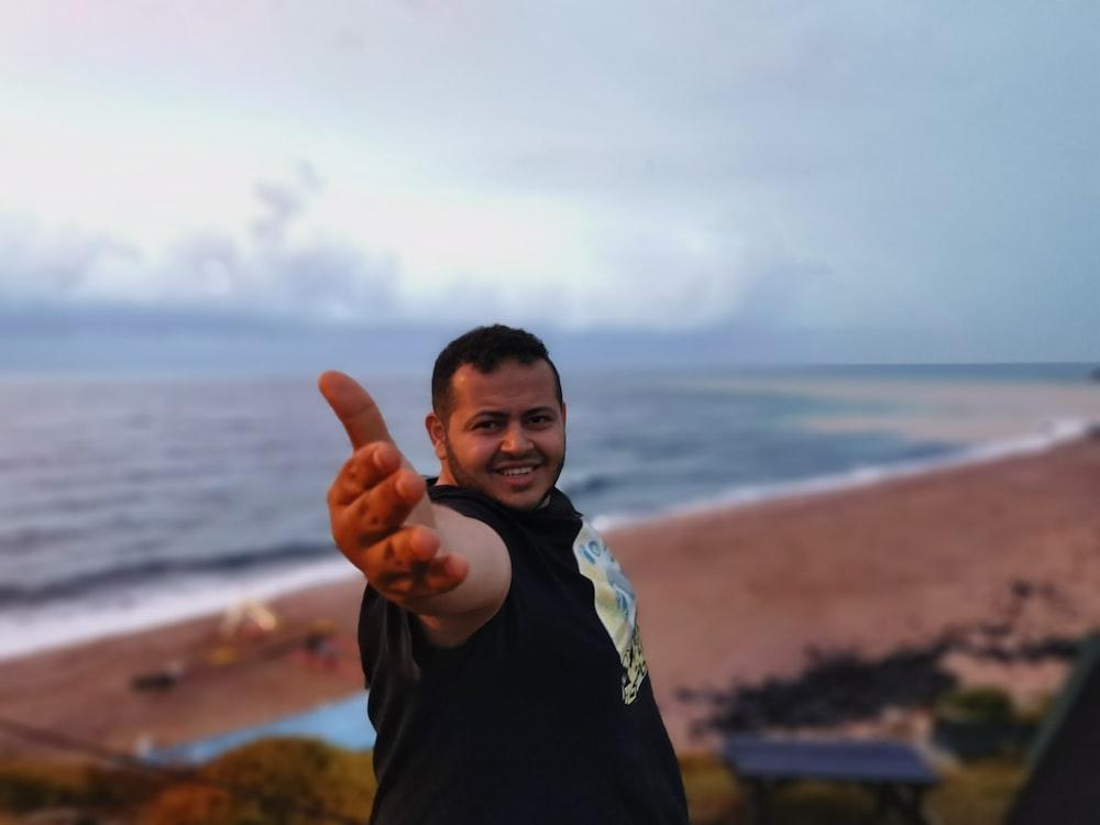 man in black t-shirt beside sea