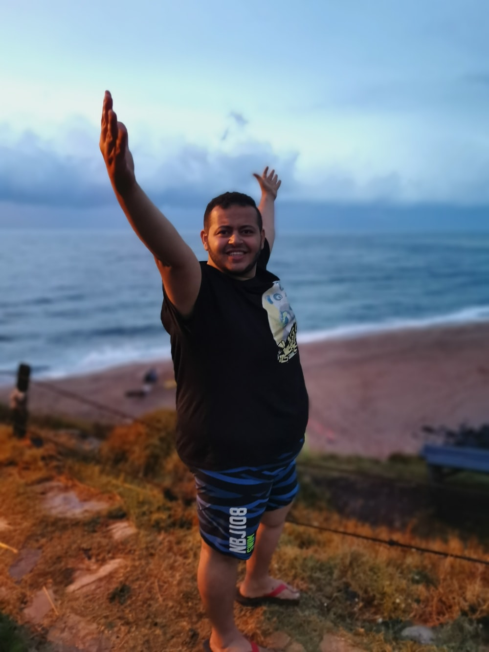 man standing beside sea during daytime