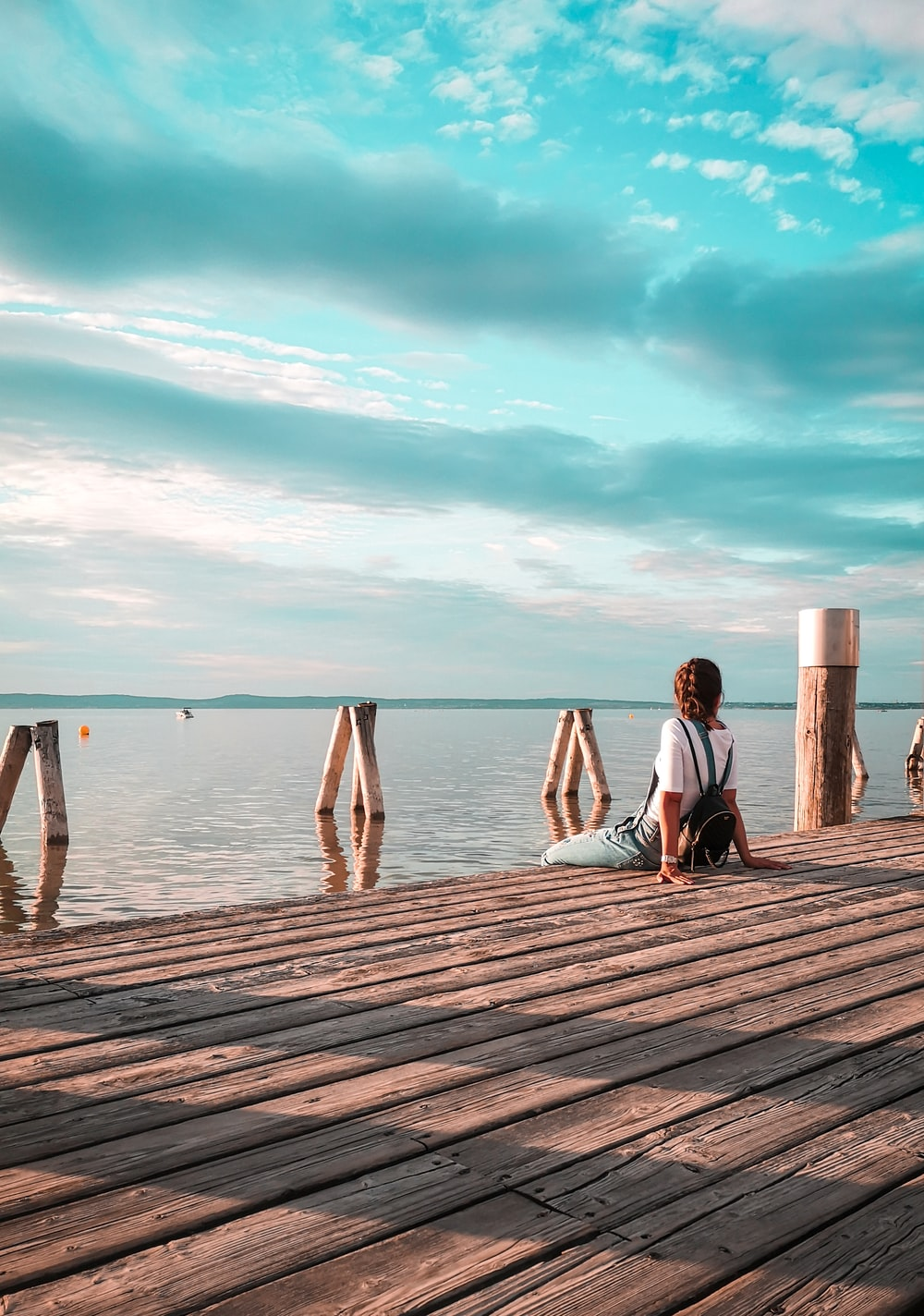 woman sitting on brown wooden dock