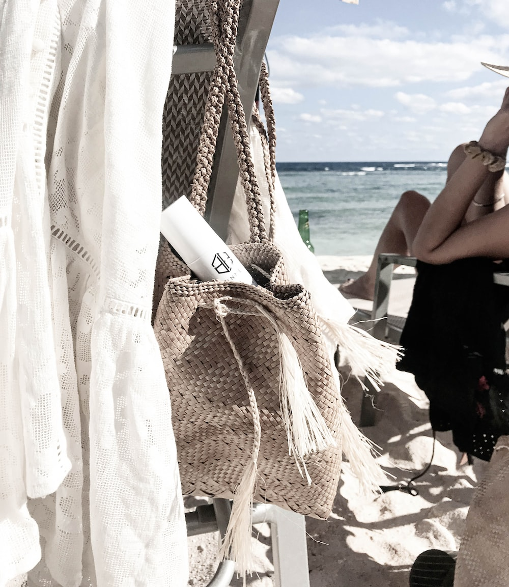 hung straw bag near sitting woman at the beach during day