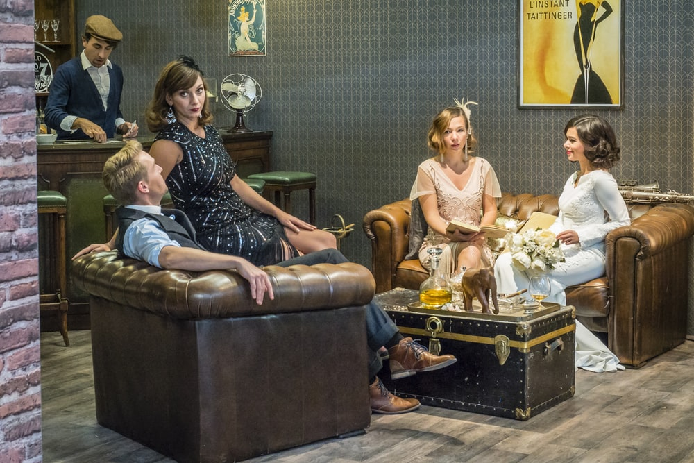 three women sitting on sofa with man inside room