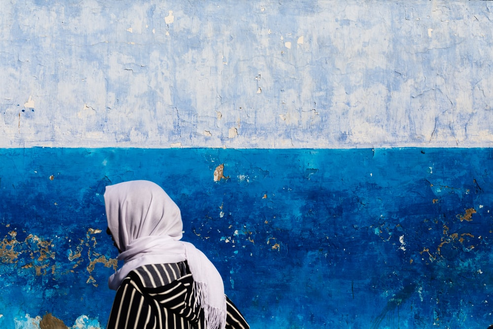 woman wearing white hijab beside blue and gray painted wall