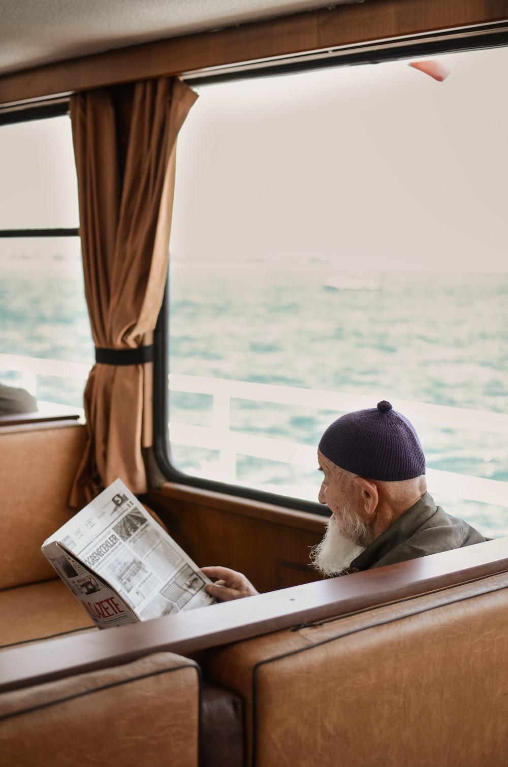 sitting man while reading newspaper