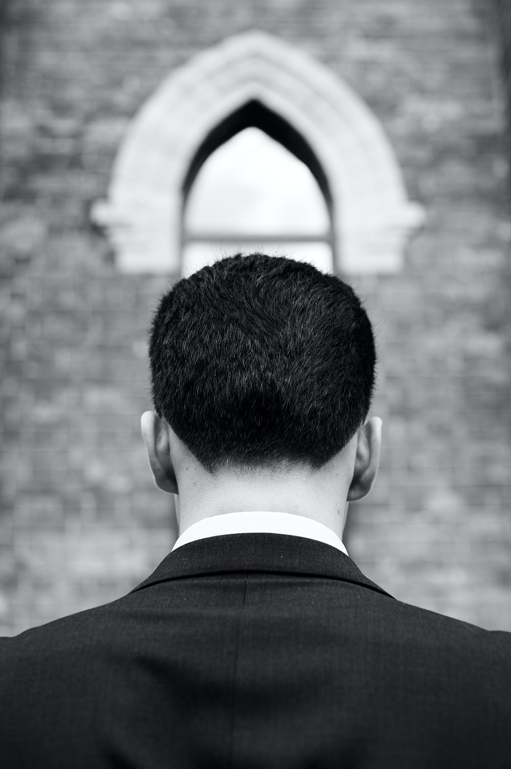 grayscale photography of man facing back near wall