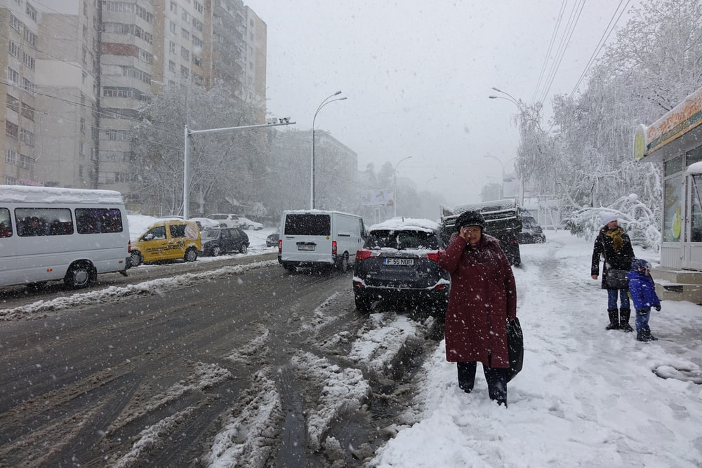 three people standing beside road covered with snow during daytime