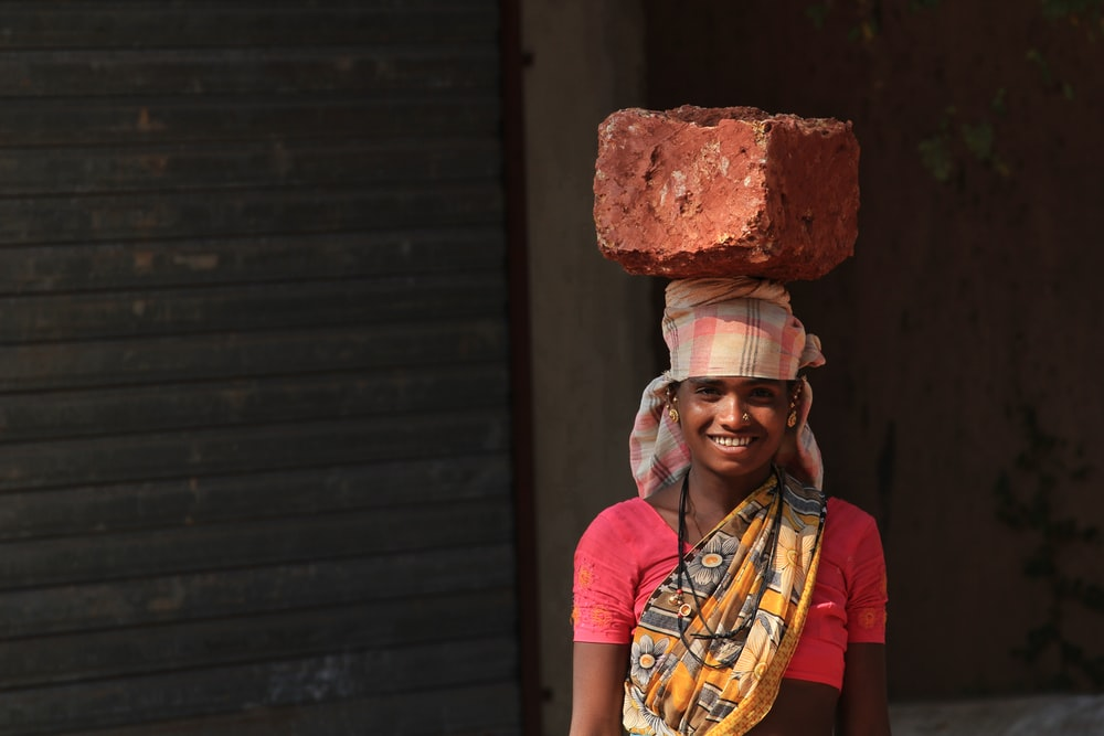 smiling woman carrying brown stone on head