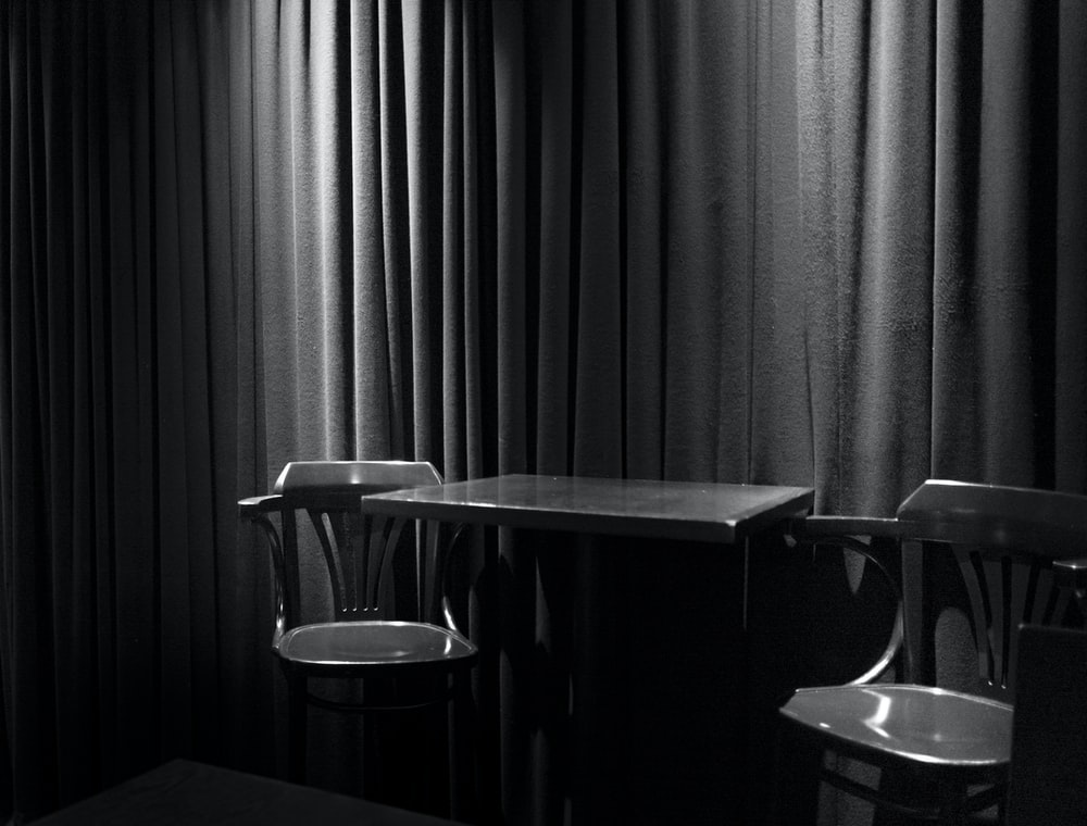 greyscale photograph of chairs beside table inside room
