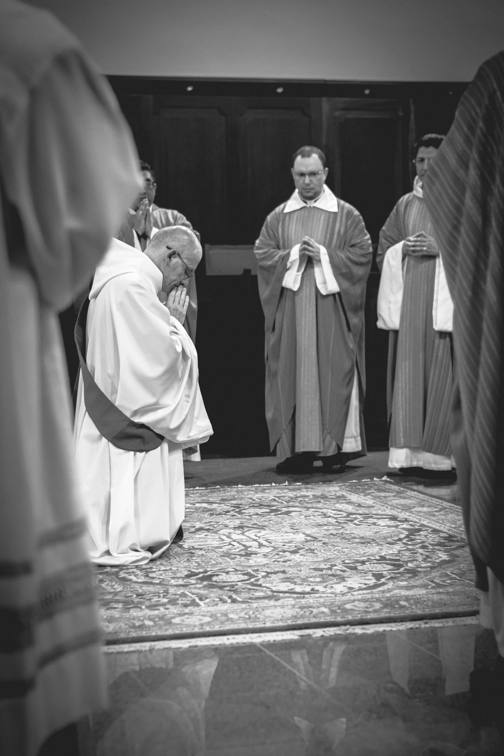 grayscale photo of priest kneeling on carpet