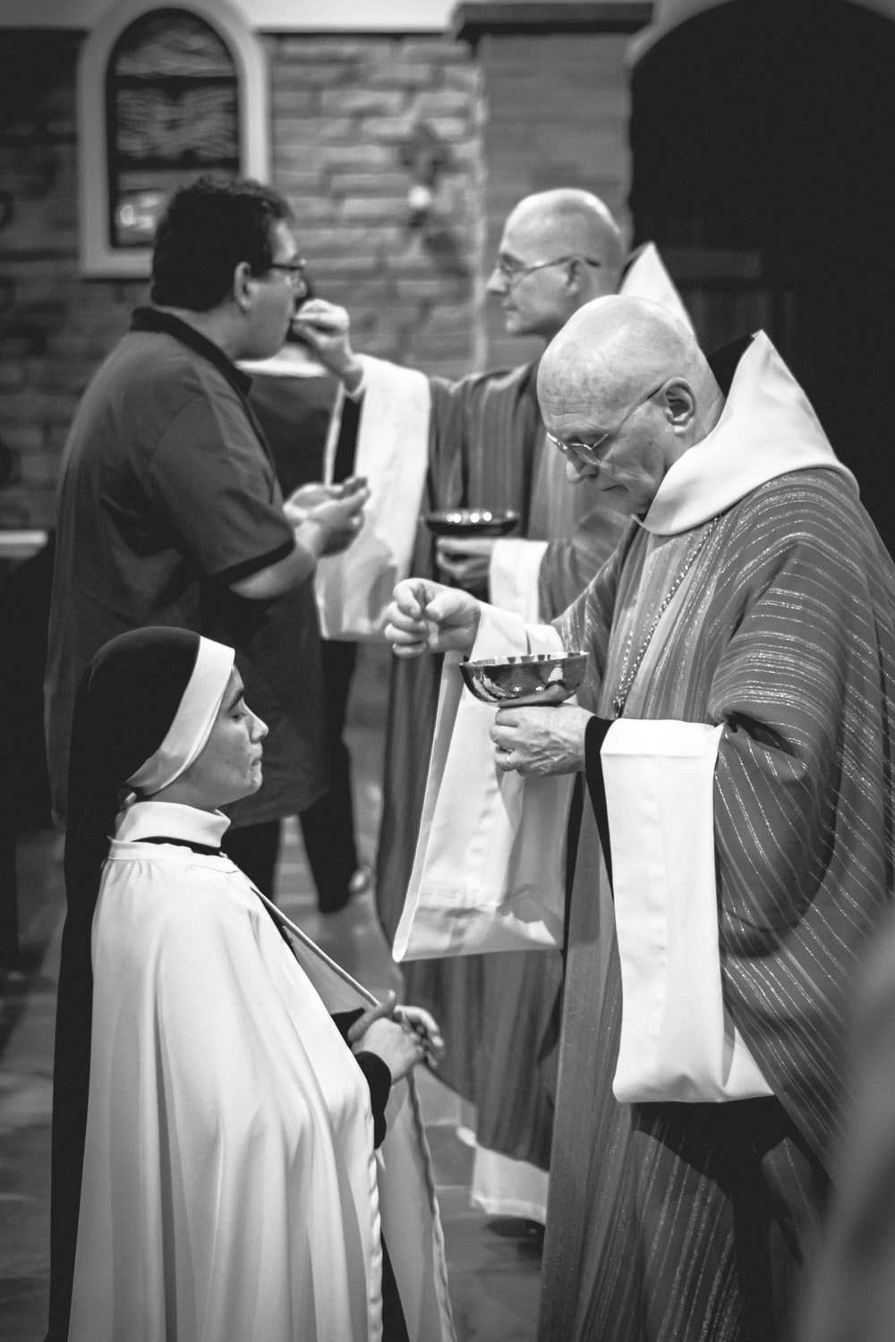 two priests giving Eucharist