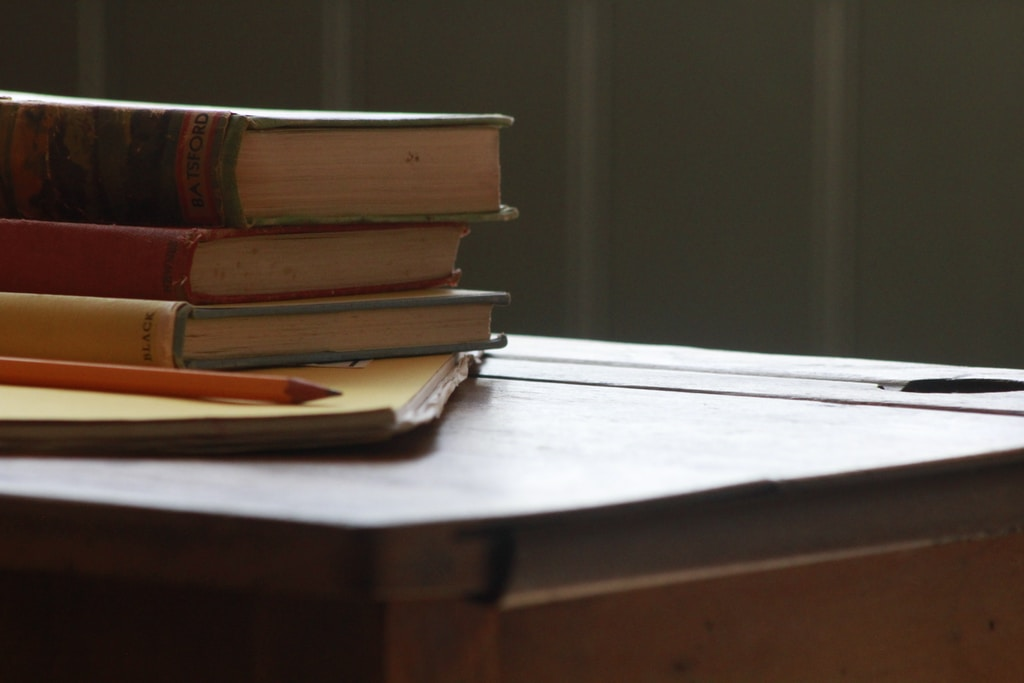 books and pencil on wooden table