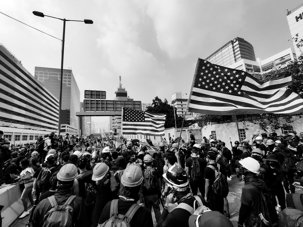 grayscale photo of people holding U.S. flag