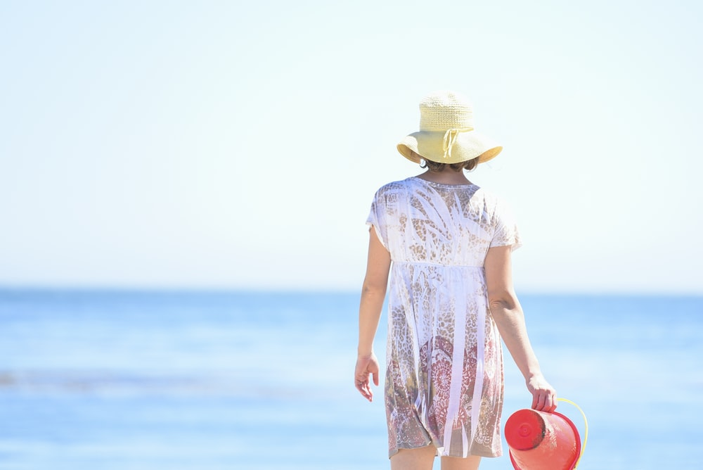 woman wearing white dress holding red plastic bucket on seashore