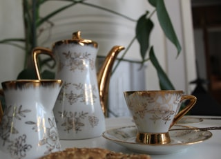 white and gold pitcher with cup and saucer
