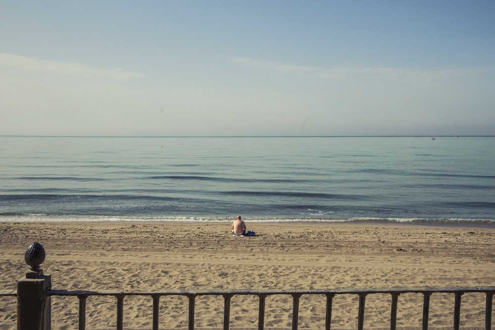person sitting on shore