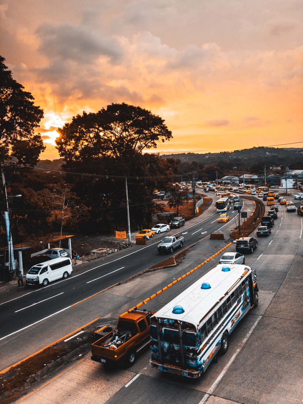 white bus and vehicles on road during golden hour