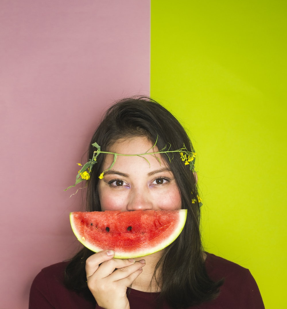 woman wearing maroon shirt holding sliced watermelon