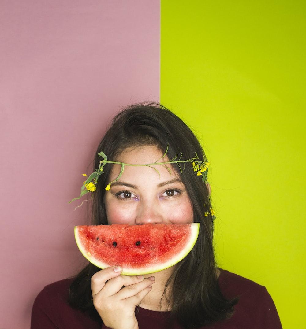 woman wearing maroon shirt holding sliced watermelon