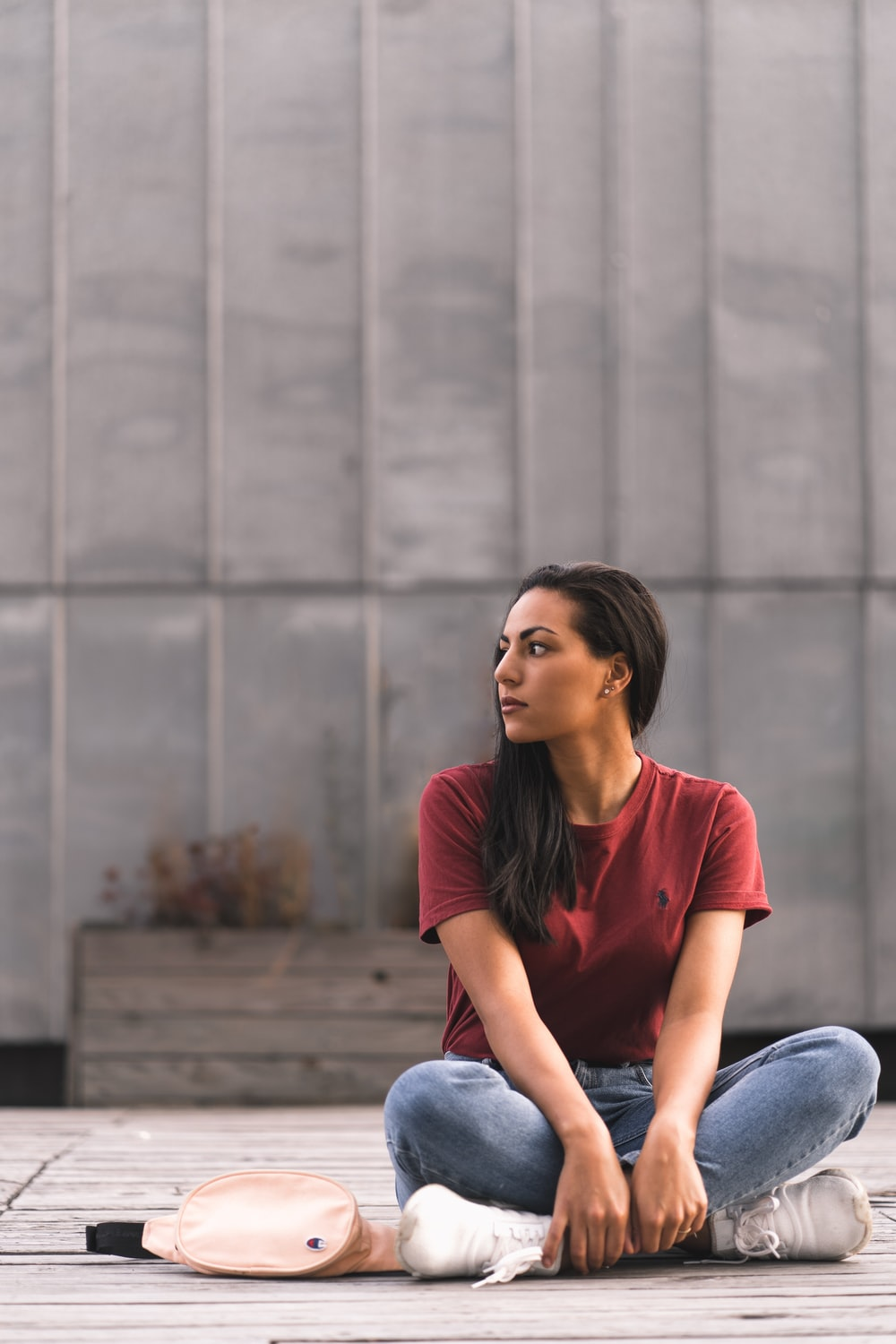 woman wearing red crew-neck shirt sitting on concrete floor