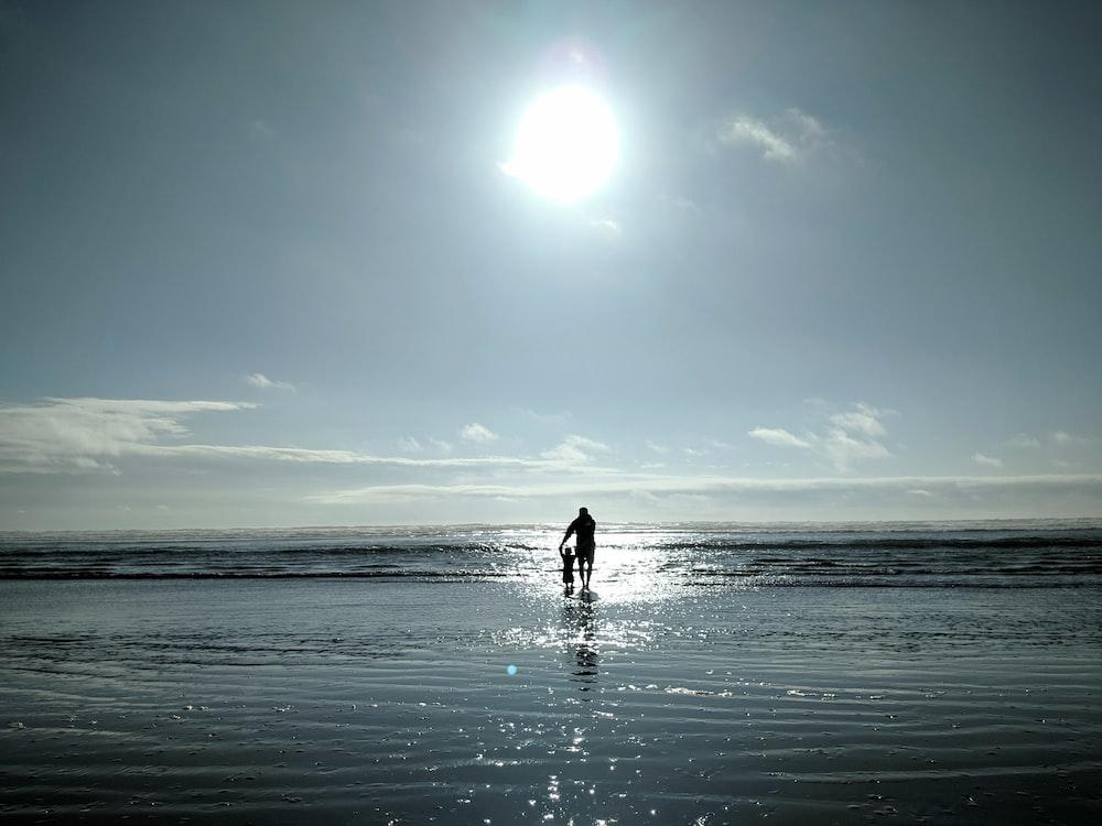 man and toddler walking on seashore