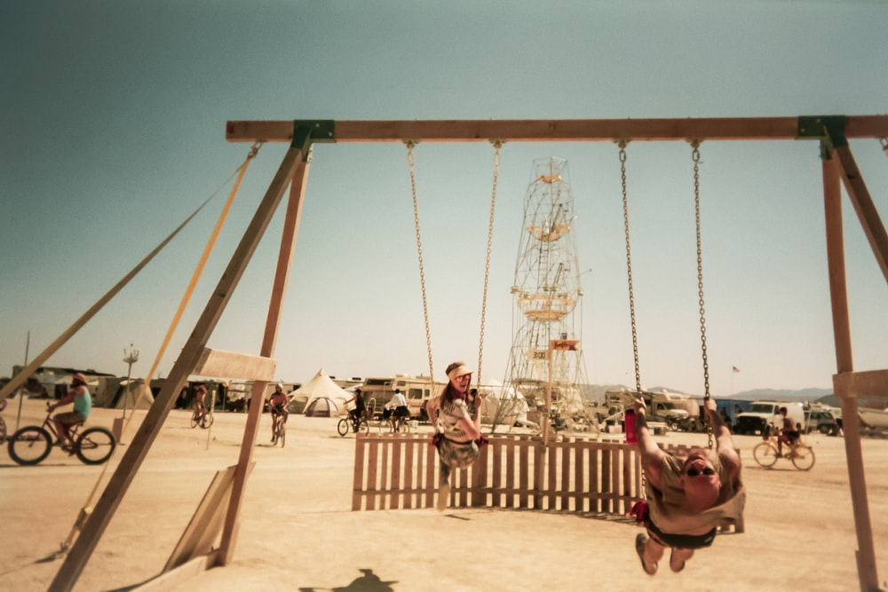 two persons riding swing during day