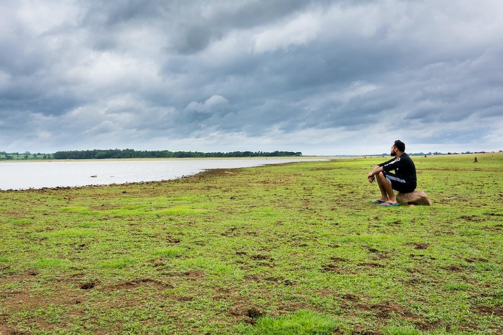 昼間の曇り空の下で緑の草の上に座っている人