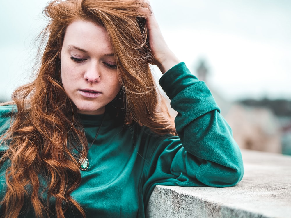 selective focus photography of woman wearing green long-sleeved top leaning on wall