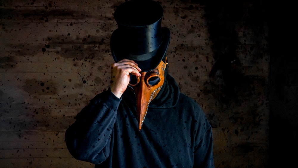 man wearing long-nosed mask and black hat