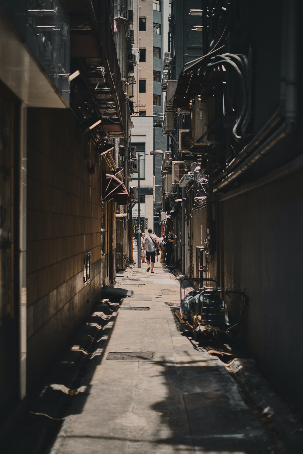 alley photography of person walkway between building during daytime