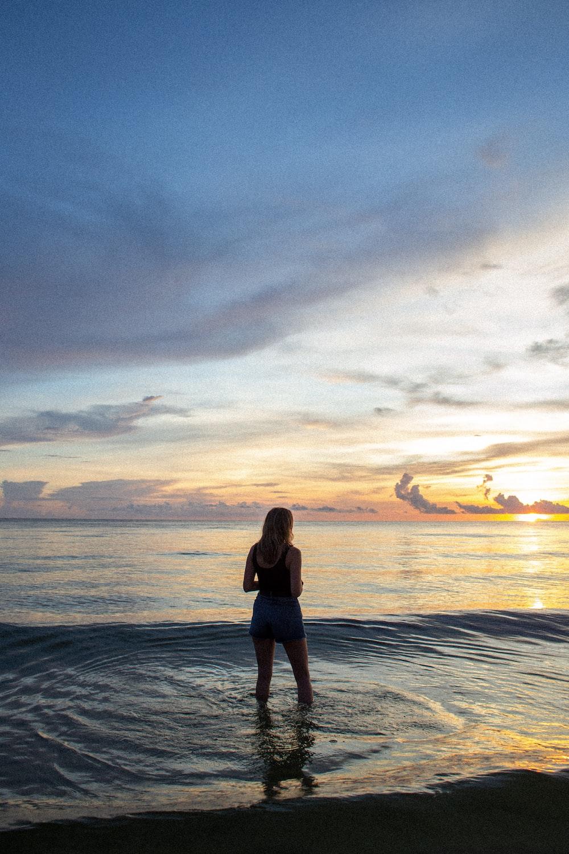 woman wearing black tank top and blue denim short standing on seashore