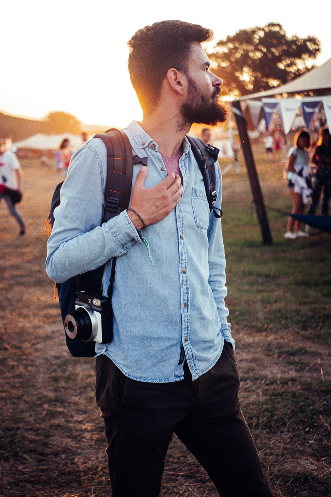 Profile picture of a music festival young male at sunset with backpack and polaroid camera, nature background.