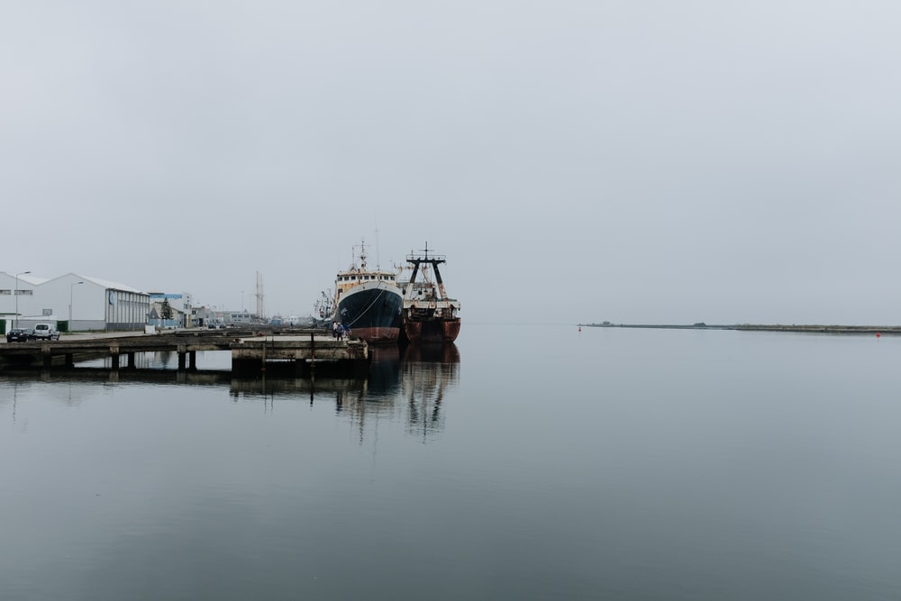 ships on dock during cloudy daytime