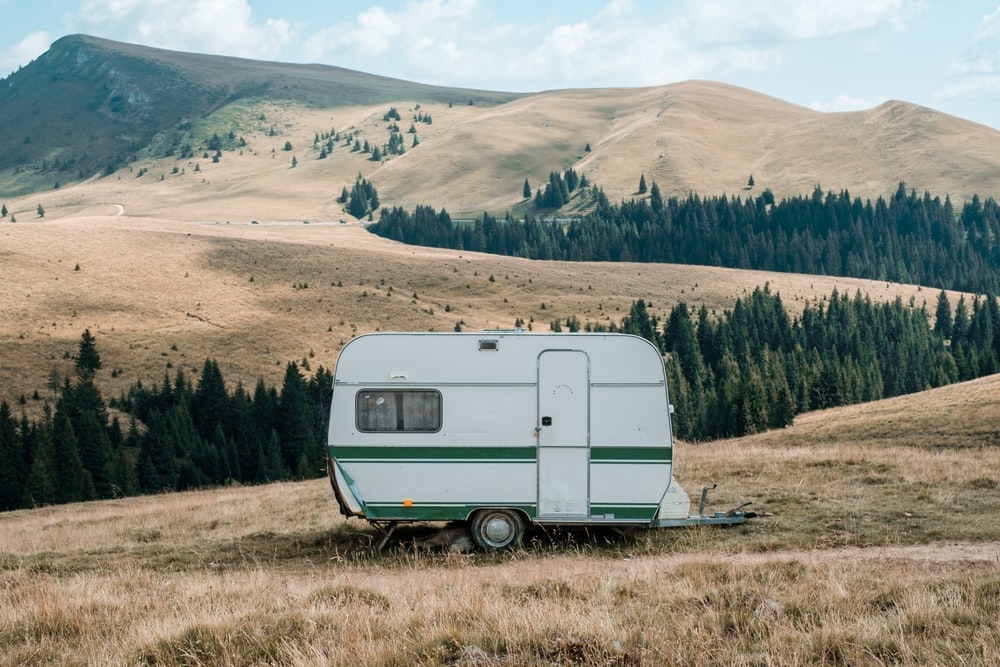 white and green RV at a brown lawn