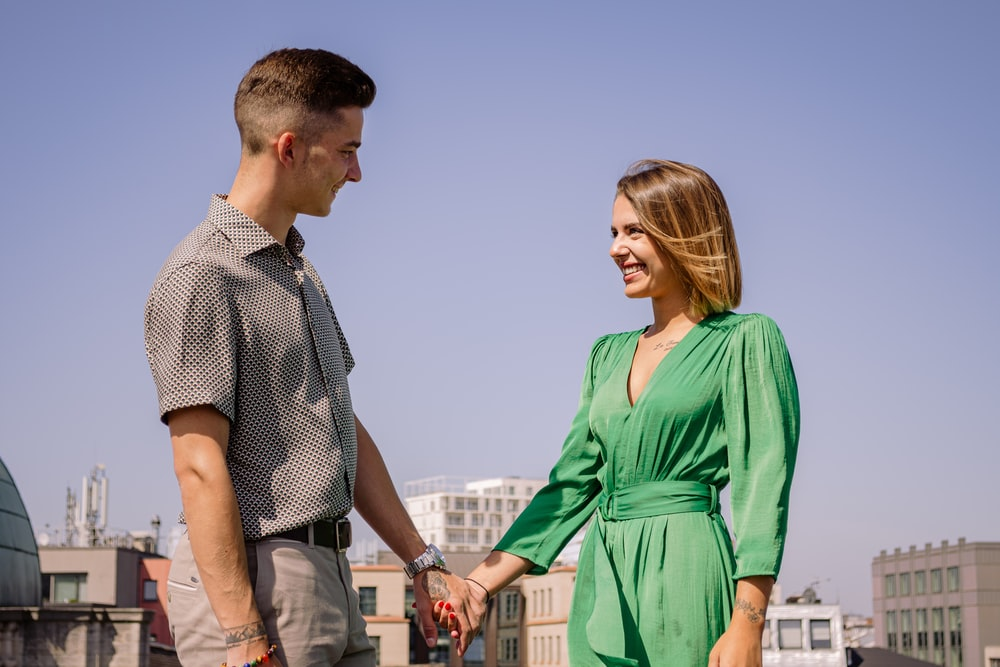 woman wearing green dress holding hands with man wearing gray polo shirt