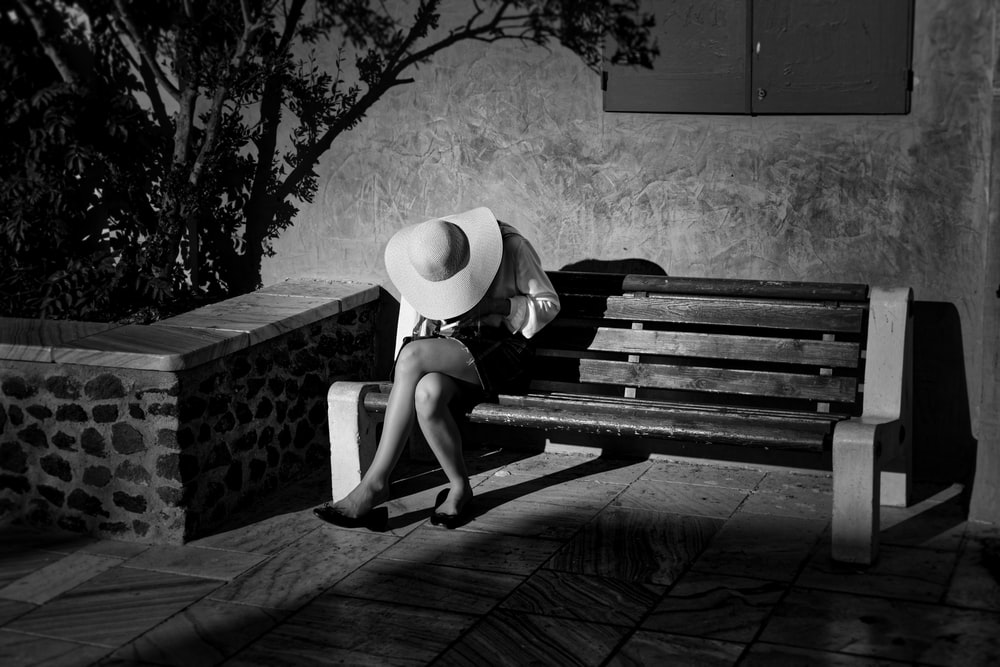 grayscale photo of woman sitting onbench