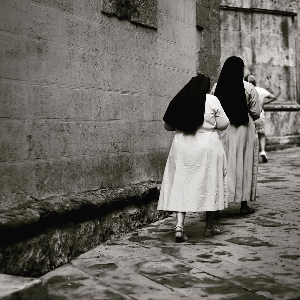 nuns walking beside building